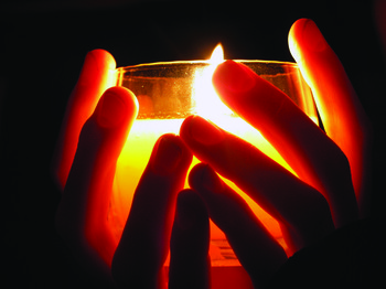 Hands holding a candle in the darkness