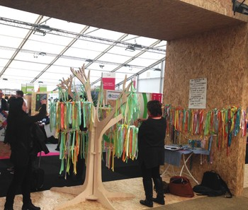 Participants write the place of the earth they love—and would hate to lose to climate change—on ribbons to hang on this Climate Ribbon Project tree.
