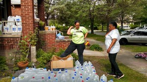Valerie Jean Bailey and Monica Lewis-Patrick set up a We the People of Detroit water station.