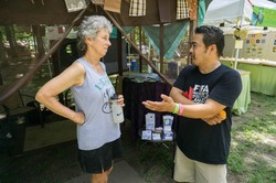 Susan Presson of Grace Covenant Presbyterian Church in Asheville, N.C., speaks with PC(USA) moderator of the 218th General Assembly (2008) Bruce Reyes Chow at the Presbyterian Hospitality tent at the Wild Goose Festival in Hot Springs, N.C.