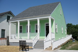 A newly constructed home in New Orleans' Lower Ninth Ward neighborhood, built to historic preservation standards, is painted by a Project Homecoming workforce crew.