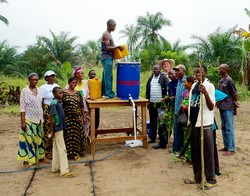 Following the installation of the drip irrigation system for the women's farming group near Kananga, everyone gathers for a photo as the drum is filled with water.