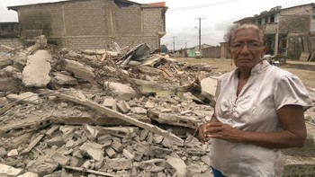 Woman stands beside the rubble that was once her home in Ecuador.