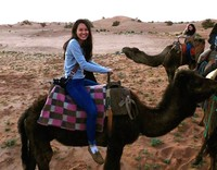 Emily Chun riding a camel in the Sahara Desert.