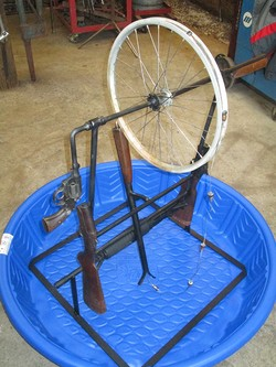 Rope pump crafted from from an AR 15 rifle, a .38 caliber handgun, and two single-barrel shotguns.