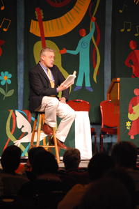 The Rev. Michael Lindvall sits in front of a multicolored  background with flowers and figures on a stool, reading a book to a  crowd.