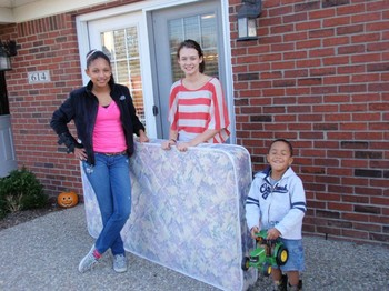 Jessica Collins, left, and a friend deliver a mattress to a boy who didn't have one.