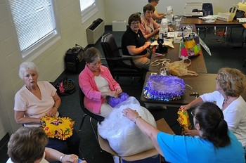 Group members stuff and assemble pillows for children in domestic abuse shelters.