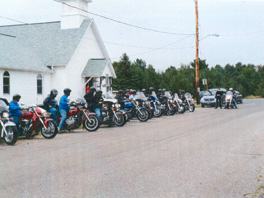 A group of people on motorcycles in a line in front of a church.