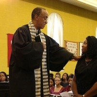 A reverend hold his hand out on CC Armstrong.