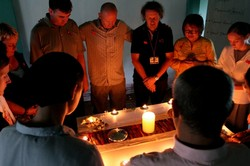 Brett Faucett (center) praying with participants in one of the training courses.