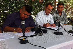 Three men sitting at a table with microphones, while two write on paper.