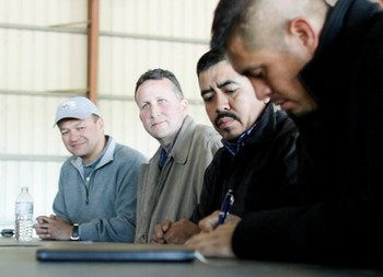 Walmart representatives John Amaya (left), Tom Leech (center) and CIW's Lucas Benitez look on as CIW's Gerardo Reyes Chavez (far right) signs historic agreement at a Lipman Produce farm outside of Immokalee.