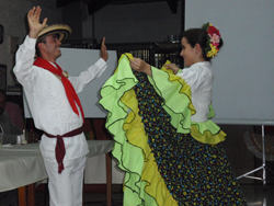 A  man in white garmets with a red neck sash and a woman in green, yellow  and polka dotted attire perform traditional dances.