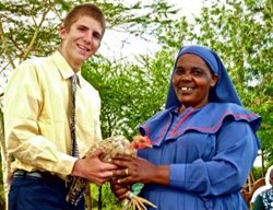 A young man and a woman in traditional Kenyan dress holding a chicken.