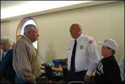 The fire chief of New London, IA, talks with members of New London Presbyterian Church at a recent community dinner sponsored by the congregation.