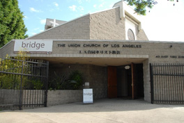 "Front view of a granite church building with the words ""The Union Church of Los Angeles"" with Japanese text below it and a white banner with the word ""Bridge"" to the left."