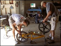 Two men repair a bicycle.