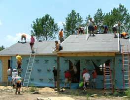 A group of people on top of a roof and surrounding the walls of a home they are building.