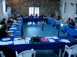 A group of people seated at tables with blue tablecloths arranged in a rectangle in a room.