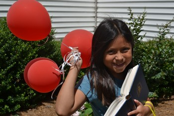 young girl holding balloons and Presbyterian hymnal