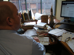 Charles Wiley, sitting at his desk with computer and files.