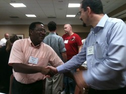 Two men shaking hands at a conference.