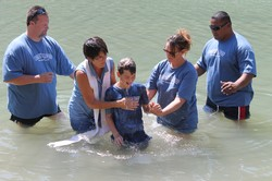 A boy is baptized by several people.
