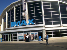 "The front entrance of a movie theater with the words ""IMAX"" in blue."