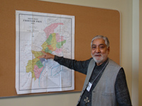 A man wearing a string name badge in grey vest and black shirt point to a map of Pakistan on a wall.