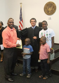 A man stands beside his children and a judge in his cloak, holding a citizenship document. An American flag and seal is behind them.