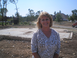 A woman stands on an empty lot, where her home once stood.