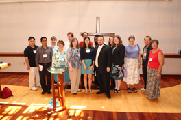 A group of seminary students dressed up, standing together in a chapel for a photo.