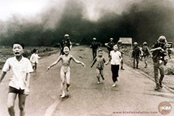 Black and white photo of people running from a napalm fire.