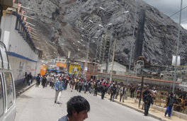A crowd standing near a building in front of a large mountain, after an attack.