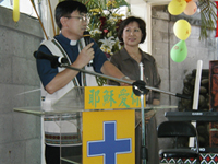 Choon and Yen Hee Lim standing together at a lecturn with yellow signs in Chinese as Choon speaks into a microphone.