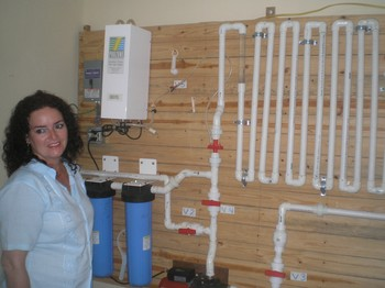 The Rev. Leticia Ramos, pastor of Prince of Peace Presbyterian Church, with the water system installed by Living Waters for the World.