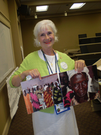 A woman holding images of Sudanese people.