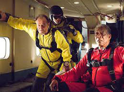 "Two three men in red and yellow jumpsuits, preparing to jump from a plane. (From the movie, ""The Bucket List."")"