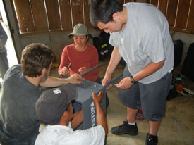 A group of people assembling a stove in a Guatemalan home.