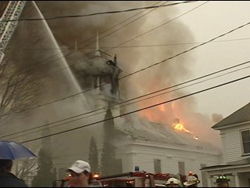 A church building on fire, surrounded by a firetruck and people