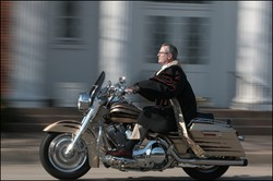 A pastor riding a motorcycle.
