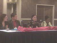 Several people at an oblong table with a red covering and microphone, as part of a panel.