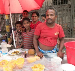 Rasel with his parents at their papaya stand.