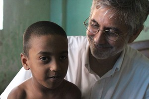 Mission co-worker Les Morgan ministers to 6-year-old Symon in Dhaka, Bangladesh.