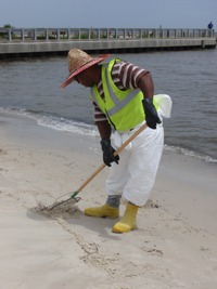A man in a bright yellow-green vest cleaning up oil from a beach.
