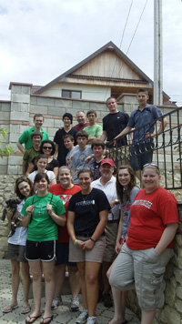 A group of volunteers standing beside a stone wall with a steel fence, on ground and stair level.
