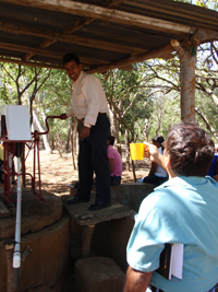 Douglas stands on a stool to pump a new well in front of several people.
