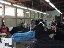 People wearing masks while working with sewing machines in a warehouse environment.