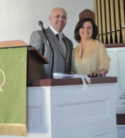 Rev. Paulo Lima with wife Zilda behind church pulpit